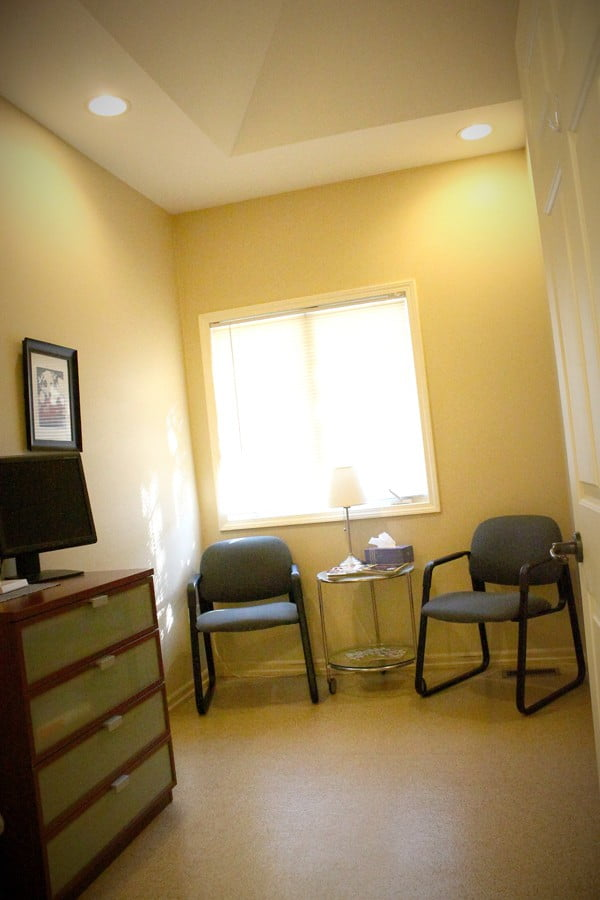 exam room with seating area and cabinet